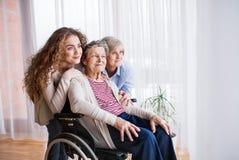Adolescente con la madre y la abuela en wheelchiar en casa Imagen de archivo libre de regalías