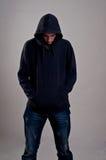 Adolescente con la maglia con cappuccio che guarda giù contro una parete grigia sporca Fotografie Stock