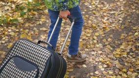 Adolescente con la maleta que camina en el pavimento metrajes