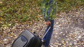 Adolescente con la maleta que camina en el pavimento almacen de video
