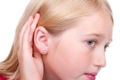 Adolescente con la mano al oído que escucha Fotografía de archivo libre de regalías
