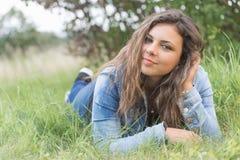 Adolescente con la mano en el pelo que miente en hierba Fotos de archivo