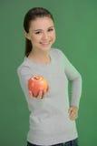 Adolescente con la manzana. Adolescente feliz que sostiene un whi de la manzana Foto de archivo