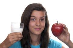 Adolescente con la manzana roja y un vidrio de leche Fotos de archivo libres de regalías
