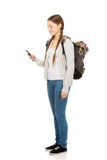 Adolescente con la mochila que envía SMS Fotografía de archivo