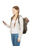 Adolescente con la mochila que envía SMS Foto de archivo libre de regalías