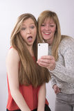 Adolescente con la mujer madura con el teléfono Fotos de archivo libres de regalías