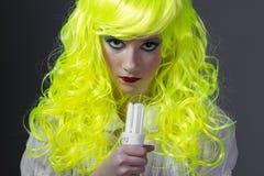 Adolescente con la peluca amarilla fluorescente, llevando una bombilla Imagenes de archivo