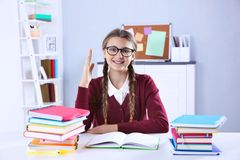 Adolescente con la pila de libros que se sientan en el escritorio en una sala de clase Foto de archivo libre de regalías