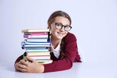 Adolescente con la pila de libros que se sientan en la tabla en el fondo blanco Imagen de archivo libre de regalías