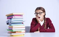 Adolescente con la pila de libros que se sientan en la tabla en el fondo blanco Foto de archivo libre de regalías