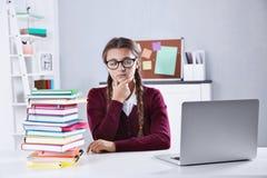 Adolescente con la pila de libros y de ordenador portátil que se sientan en el escritorio en una sala de clase Imagen de archivo libre de regalías