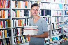 Adolescente con la pila del libro en tienda Fotografía de archivo libre de regalías