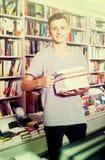 Adolescente con la pila del libro en tienda Imágenes de archivo libres de regalías