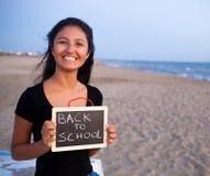 Adolescente con la pizarra en la playa Concepto de nuevo a escuela Imagen de archivo