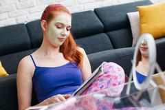 Adolescente con la revista y la relajación de la lectura de la máscara de la belleza Imagen de archivo