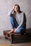 Adolescente con la rodilla doblada que se sienta en una cubierta Fondo gris Fotos de archivo