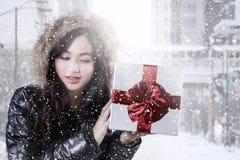 Adolescente con la ropa del invierno que sostiene la caja de regalo Fotografía de archivo