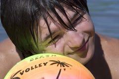 Adolescente con la sfera sulla spiaggia Fotografie Stock