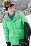 Adolescente con la snowboard el día de fiesta del esquí Imágenes de archivo libres de regalías