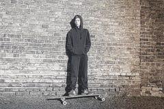 Adolescente con la sudadera con capucha que se coloca en un tablero largo Fotografía de archivo
