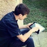 Adolescente con la tableta al aire libre Fotos de archivo libres de regalías