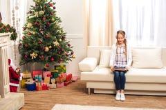 Adolescente con la tableta digital en el christmastime Imagenes de archivo