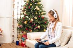 Adolescente con la tableta digital en el christmastime Imagen de archivo