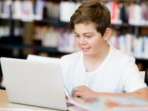 Adolescente con la tableta en biblioteca Fotografía de archivo