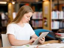 Adolescente con la tableta en biblioteca Fotos de archivo libres de regalías