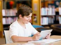 Adolescente con la tableta en biblioteca Imagen de archivo