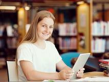 Adolescente con la tableta en biblioteca Fotos de archivo