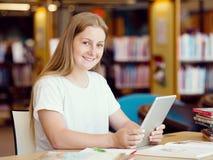 Adolescente con la tableta en biblioteca Foto de archivo libre de regalías