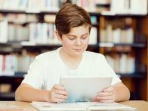 Adolescente con la tableta en biblioteca Fotografía de archivo libre de regalías
