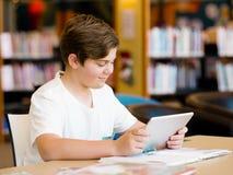Adolescente con la tableta en biblioteca Imagenes de archivo