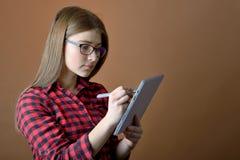 Adolescente con la tableta en casa Fotografía de archivo