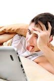 Adolescente con la tableta en la cama Fotografía de archivo libre de regalías