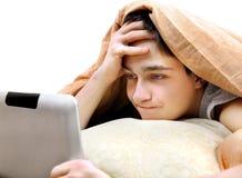 Adolescente con la tableta en la cama Imágenes de archivo libres de regalías