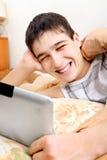 Adolescente con la tableta en la cama Imagenes de archivo