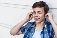 Adolescente con la tableta que se sienta cerca de la pared Imagen de archivo libre de regalías