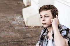 Adolescente con la tableta que se sienta cerca de la pared Imagen de archivo
