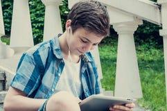Adolescente con la tableta que se sienta en las escaleras Imagen de archivo libre de regalías