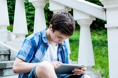 Adolescente con la tableta que se sienta en las escaleras Foto de archivo libre de regalías