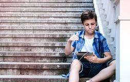 Adolescente con la tableta que se sienta en las escaleras Imagen de archivo
