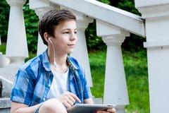 Adolescente con la tableta que se sienta en las escaleras Foto de archivo