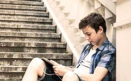 Adolescente con la tableta que se sienta en las escaleras Fotos de archivo