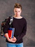 Adolescente con la taleguilla y libros que parecen enojados Fotos de archivo