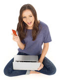 Adolescente con la tarjeta de crédito y el ordenador portátil Foto de archivo libre de regalías