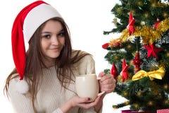 Adolescente con la taza de café debajo del árbol de navidad Foto de archivo