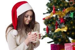 Adolescente con la taza de café debajo del árbol de navidad Foto de archivo libre de regalías